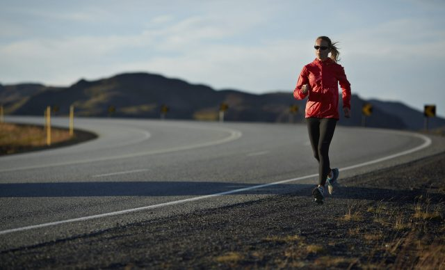 Woman running on big road, mountains in background